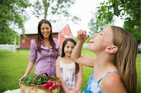 eating - Family Party. Two Young Girls Standing By A Table, One Eating A Fresh Ripe Cherry. A Young Woman Carrying A Bowl Of Salad. Stock Photo - Premium Royalty-Free, Code: 6118-07122179