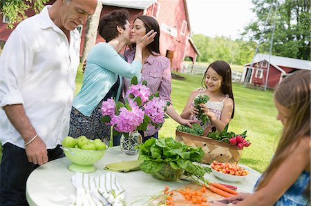 Family Party. A Table Laid With Salads And Fresh Fruits And Vegetables. Parents And Children. A Mother Kissing A Daughter On The Cheek. Stock Photo - Premium Royalty-Free, Code: 6118-07122187