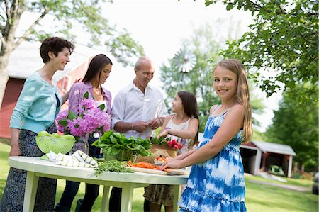 Family Party. A Table Laid With Salads And Fresh Fruits And Vegetables. Parents And Children. Two Girls, One Young Woman And A Mature Couple. Stock Photo - Premium Royalty-Free, Code: 6118-07122184