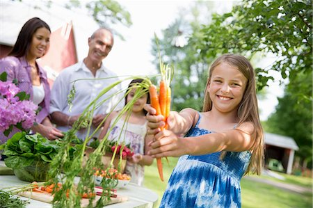 Family Party. A Table Laid With Salads And Fresh Fruits And Vegetables. Parents And Children. A Child Holding Out Fresh Picked Carrots. Stock Photo - Premium Royalty-Free, Code: 6118-07122185