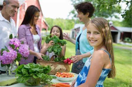 Family Party. A Table Laid With Salads And Fresh Fruits And Vegetables. Parents And Children. Stock Photo - Premium Royalty-Free, Code: 6118-07122189