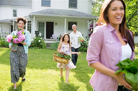 Family Party. Parents And Children Walking Across The Lawn Carrying Flowers, Fresh Picked Vegetables And Fruits. Preparing For A Party. Stock Photo - Premium Royalty-Free, Code: 6118-07122193