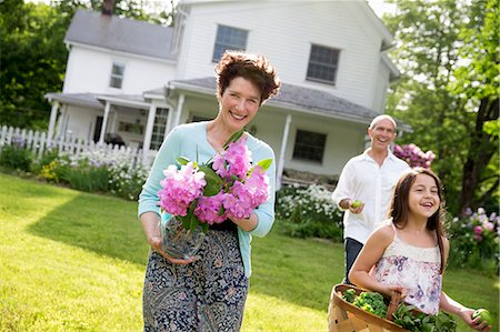 Family Party. Parents And Children Walking Across The Lawn Carrying Flowers, Fresh Picked Vegetables And Fruits. Preparing For A Party. Stock Photo - Premium Royalty-Free, Code: 6118-07122194