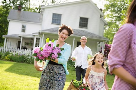 front - Family Party. Parents And Children Walking Across The Lawn Carrying Flowers, Fresh Picked Vegetables And Fruits. Preparing For A Party. Stock Photo - Premium Royalty-Free, Code: 6118-07122196