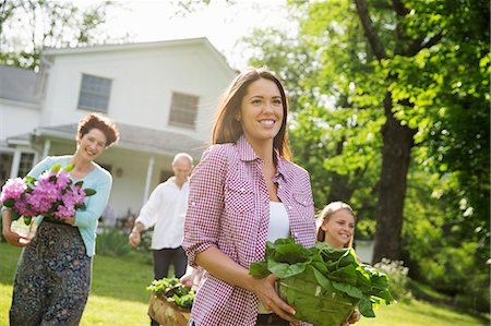 Family Party. Parents And Children Walking Across The Lawn Carrying Flowers, Fresh Picked Vegetables And Fruits. Preparing For A Party. Stock Photo - Premium Royalty-Free, Code: 6118-07122198