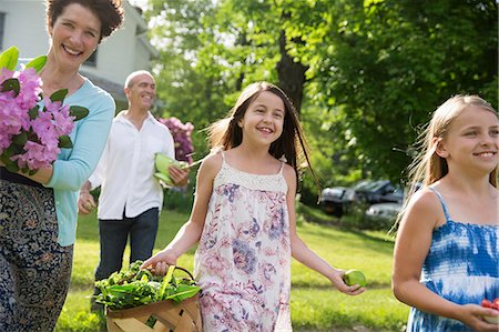 Family Party. Parents And Children Walking Across The Lawn Carrying Flowers, Fresh Picked Vegetables And Fruits. Preparing For A Party. Stock Photo - Premium Royalty-Free, Code: 6118-07122199