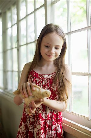 A Young Girl In A Floral Sundress, Holding A Young Chick Carefully In Her Hands. Stock Photo - Premium Royalty-Free, Code: 6118-07122240