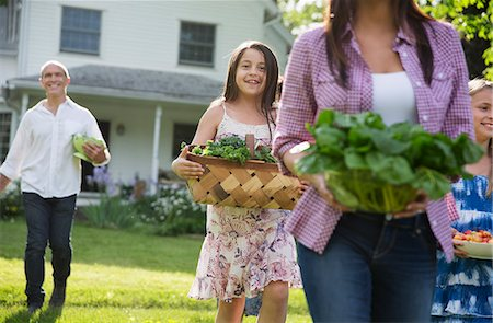 Family Party. Parents And Children Walking Across The Lawn Carrying Flowers, Fresh Picked Vegetables And Fruits. Preparing For A Party. Stock Photo - Premium Royalty-Free, Code: 6118-07122203