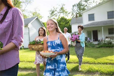 Family Party. Parents And Children Walking Across The Lawn Carrying Flowers, Fresh Picked Vegetables And Fruits. Preparing For A Party. Stock Photo - Premium Royalty-Free, Code: 6118-07122200