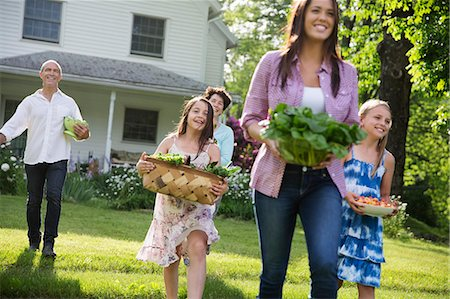 Family Party. Parents And Children Walking Across The Lawn Carrying Flowers, Fresh Picked Vegetables And Fruits. Preparing For A Party. Stock Photo - Premium Royalty-Free, Code: 6118-07122202