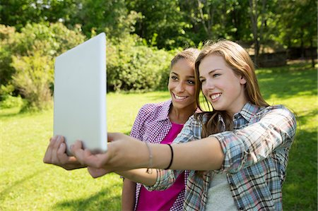 preteen touch - Two Girls Sitting Outdoors On A Bench, Using A Digital Tablet. Holding It Out At Arm's Length. Stock Photo - Premium Royalty-Free, Code: 6118-07122217