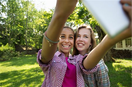 preteen touch - Two Girls Sitting Outdoors On A Bench, Using A Digital Tablet. Holding It Out At Arm's Length. Stock Photo - Premium Royalty-Free, Code: 6118-07122219