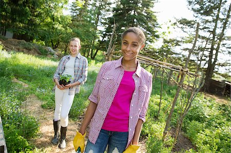 preteen touch - Two Girls In A Garden, Walking Up The Path, One Carrying A Plant In A Pot. Stock Photo - Premium Royalty-Free, Code: 6118-07122234