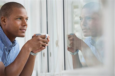 Office. A Young Man Leaning On The Windowsill Holding A Cup Of Tea. Stock Photo - Premium Royalty-Free, Code: 6118-07122352