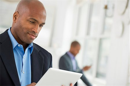 settlement - Business People. A Man In A Business Suit Using A Digital Tablet. Stock Photo - Premium Royalty-Free, Code: 6118-07122361