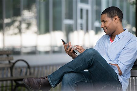 people sitting on bench - Summer In The City. People Outdoors, Keeping In Touch While On The Move. A Man Sitting On A Bench Using A Digital Tablet. Stock Photo - Premium Royalty-Free, Code: 6118-07122300