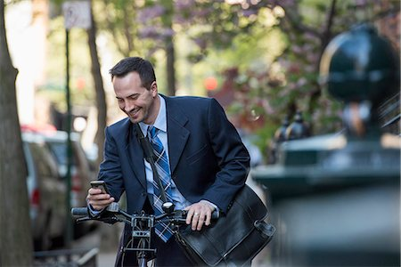 settlement - A Man In A Business Suit, Outdoors In A Park. Sitting On A Bicycle. Stock Photo - Premium Royalty-Free, Code: 6118-07122474