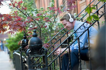 A Man In A Blue Shirt Wearing Headphones And Listening To A Music Player. Foto de stock - Sin royalties Premium, Código: 6118-07122483