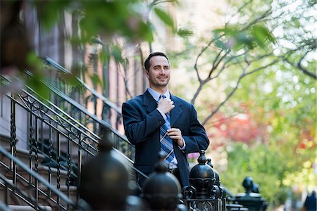 A Man In A Business Suit Adjusting His Tie. At The Bottom Of The Steps Of A Townhouse In A Terrace. Stock Photo - Premium Royalty-Free, Code: 6118-07122482