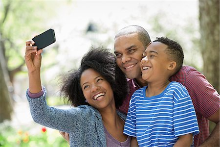 Two Adults And A Young Boy Taking Photographs With A Smart Phone. Stock Photo - Premium Royalty-Free, Code: 6118-07122499