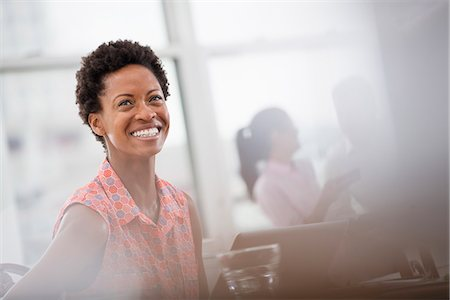 Office Life. A Young Woman In A Pink Shirt Laughing. Stock Photo - Premium Royalty-Free, Code: 6118-07122418