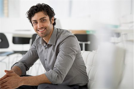 Business. A Man Seated With His Hands Clasped In A Relaxed Pose. Smiling And Leaning Forwards. Stock Photo - Premium Royalty-Free, Code: 6118-07122556