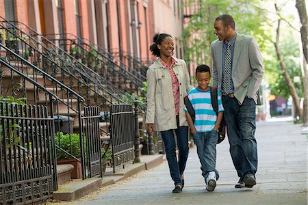 A Family Outdoors In The City. Two Parents And A Young Boy Walking Together. Stock Photo - Premium Royalty-Free, Code: 6118-07122527
