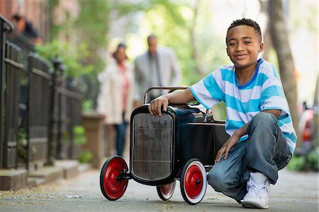 A Young Boy Playing With A Old Fashioned Toy Car On Wheels On A City Street. A Couple Looking On. Stock Photo - Premium Royalty-Free, Code: 6118-07122532