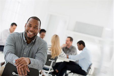 Office Interior. A Man Seated Separately From A Group Of People Seated Around A Table. A Business Meeting. Stock Photo - Premium Royalty-Free, Code: 6118-07122693