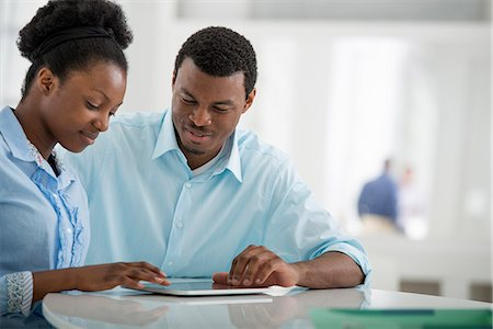 Office Interior. A Man And Woman Sitting Side By Side Using A Digital Tablet. Stock Photo - Premium Royalty-Free, Code: 6118-07122636