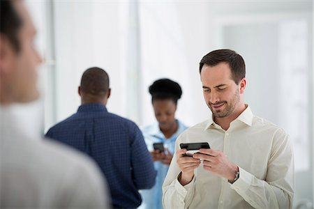 Office Interior. A Group Of People, One Man Using A Smart Phone. Stock Photo - Premium Royalty-Free, Code: 6118-07122639