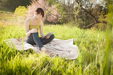 scenic and spring (season) - A Young Woman Sitting In A Field, On A Blanket, Reading From A Digital Tablet. Stock Photo - Premium Royalty-Free, Code: 6118-07122740