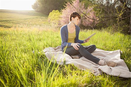 season - A Young Woman Sitting In A Field, On A Blanket, Holding And Looking At The Screen Of A Digital Tablet. Working Outdoors. Stock Photo - Premium Royalty-Free, Code: 6118-07122741
