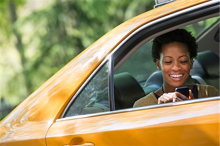 settlement - A Woman Sitting In The Rear Passenger Seat Of A Yellow Cab, Checking Her Phone. Stock Photo - Premium Royalty-Free, Code: 6118-07122772