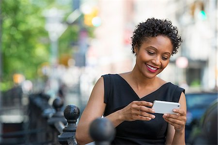 settlement - People On The Move. A Woman In A Black Dress On A City Street, Checking Her Phone. Stock Photo - Premium Royalty-Free, Code: 6118-07122780