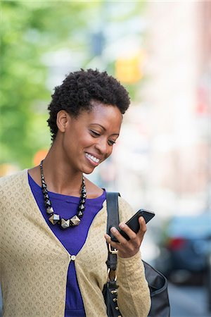 City. A Woman In A Purple Dress Checking Her Smart Phone. Stock Photo - Premium Royalty-Free, Code: 6118-07122785