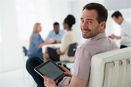 settlement - Office Interior. Meeting. One Person Looking Over His Shoulder And Away From The Group. Holding A Digital Tablet. Stock Photo - Premium Royalty-Free, Code: 6118-07122703