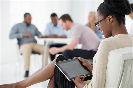 settlement - Office Interior. Meeting. One Person Seated Separately, Using A Tablet Computer. Holding A Digital Tablet. Stock Photo - Premium Royalty-Free, Code: 6118-07122700