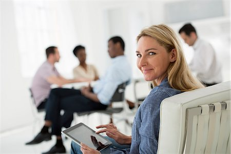 Office Interior. Meeting. One Person Looking Over Her Shoulder And Away From The Group. Holding A Digital Tablet. Stock Photo - Premium Royalty-Free, Code: 6118-07122705