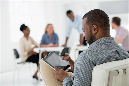 settlement - Office Interior. Meeting. One Person Seated Separately, Using A Tablet Computer. Holding A Digital Tablet. Stock Photo - Premium Royalty-Free, Code: 6118-07122708
