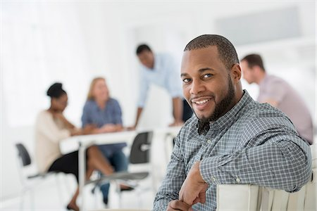 settlement - Office Interior. Meeting. One Person Looking Over Her Shoulder And Away From The Group. Stock Photo - Premium Royalty-Free, Code: 6118-07122710
