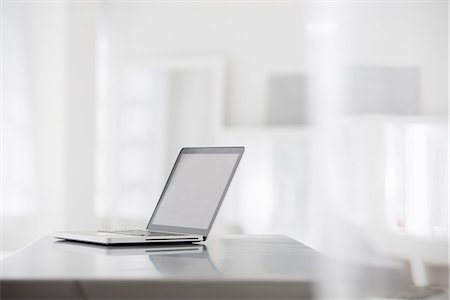 selective focus computer no people - Office Interior. A Smooth Shiny Grey Tabletop, And An Open Laptop Computer. Stock Photo - Premium Royalty-Free, Code: 6118-07122714