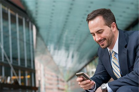 settlement - City. A Man In A Business Suit Checking His Messages On His Smart Phone. Stock Photo - Premium Royalty-Free, Code: 6118-07122841