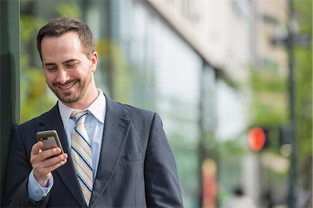 settlement - City. A Man In A Business Suit Checking His Messages On His Smart Phone. Stock Photo - Premium Royalty-Free, Code: 6118-07122829