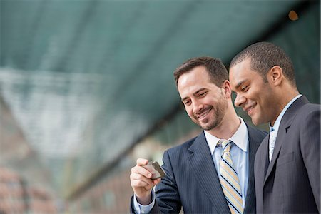 settlement - City. Two Men In Business Suits, Looking At A Smart Phone, Smiling. Stock Photo - Premium Royalty-Free, Code: 6118-07122838