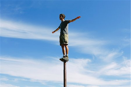 Man standing and balancing on a metal post, looking towards expansive sky, on Surprise Mountain, Alpine Lakes Wilderness, Mt. Baker-Snoqualmie National forest. Stock Photo - Premium Royalty-Free, Code: 6118-07202948