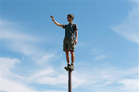Man standing and balancing on a metal post, looking towards expansive sky, on Surprise Mountain, Alpine Lakes Wilderness, Mt. Baker-Snoqualmie national forest. Stock Photo - Premium Royalty-Free, Code: 6118-07202950