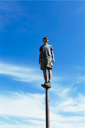 Man standing and balancing on a metal post, looking towards expansive sky, Surprise Mountain, Alpine Lakes Wilderness, Mt. Baker-Snoqualmie National Forest. Stock Photo - Premium Royalty-Free, Code: 6118-07202951