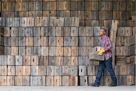 A farmyard. A stack of traditional wooden crates for packing fruit and vegetables. A man carrying an empty crate. Stock Photo - Premium Royalty-Free, Code: 6118-07203028