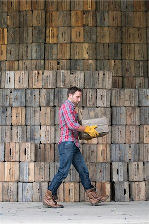 A farmyard. A stack of traditional wooden crates for packing fruit and vegetables. A man carrying an empty crate. Stock Photo - Premium Royalty-Free, Code: 6118-07203029